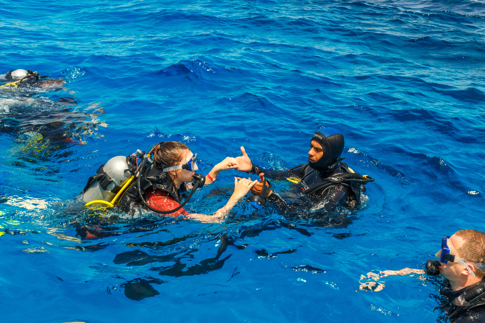 group of people taking scuba diving lessons in swimming pool
