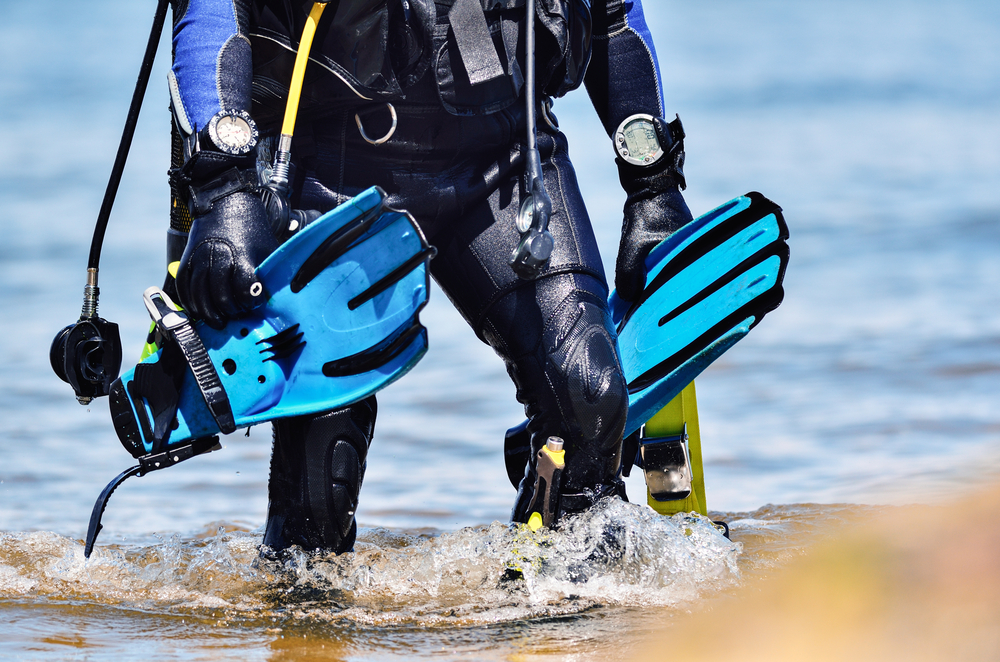 scuba diver walking with gear and dive accessories